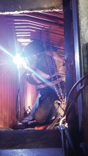 A person welding a boiler in a confined space