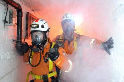 Two people in a confined space, wearing breathing apparatus surrounded by smoke