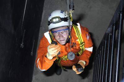 A person looking up from a confined space in a harness