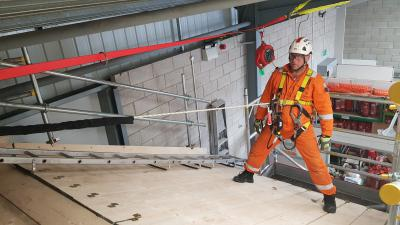 A man in PPE using a rope on a sloped roof