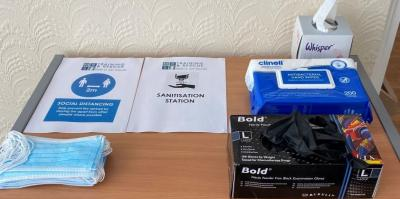 Facemasks and nitrile disposable gloves for delegates on a desk